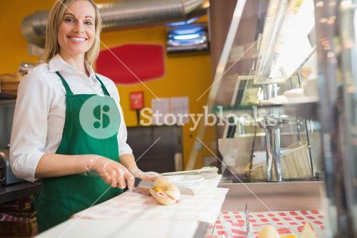 Female worker cutting sandwich on counter