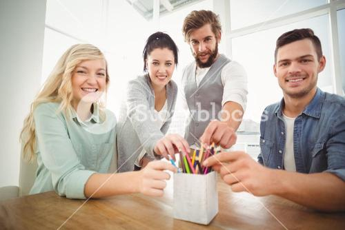 Portrait of smiling business people taking pencils from desk organizer