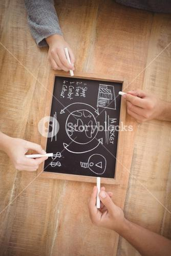 Cropped hands holding chalk with business terms on slate