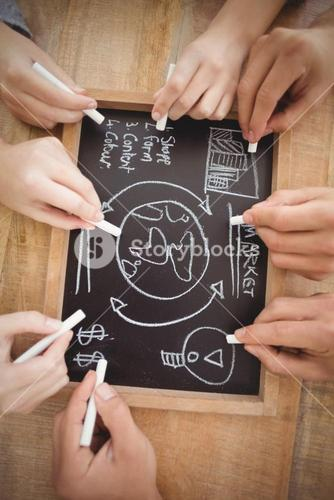 Overhead view of cropped hands writing business terms on slate