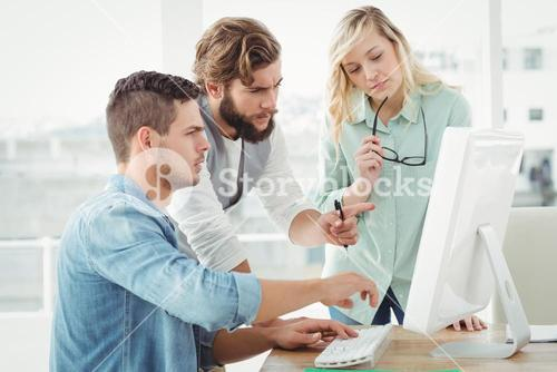 Business people discussing by computer
