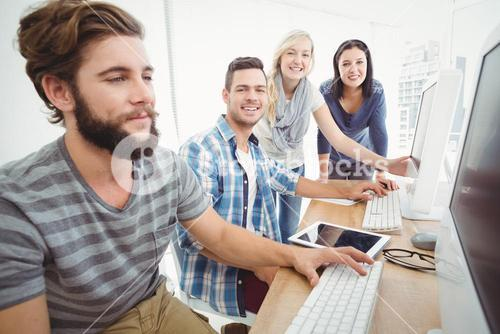 Cheerful business team at computer desk