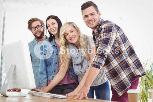 Portrait of smiling business people working at computer desk