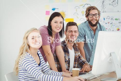 Portrait of smiling business professionals working at computer desk