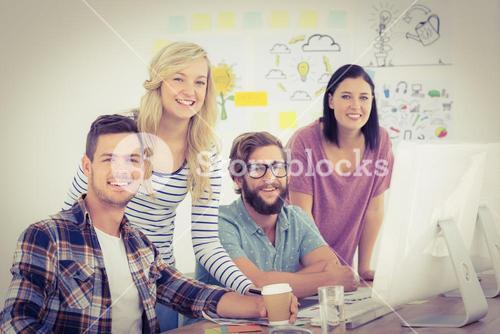 Portrait of happy business professionals working at computer desk