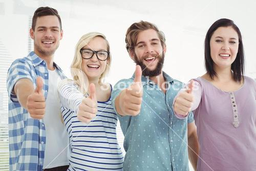 Portrait of cheerful business people with thumbs up