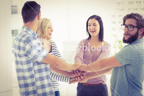 Smiling business people putting their hands together