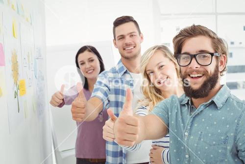 Portrait of smiling business people with thumbs up