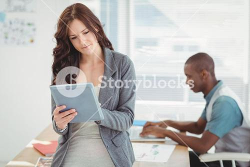 Woman using digital tablet with man working at desk