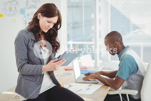 Woman using digital tablet while sitting on desk with man working