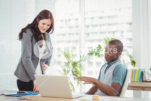 Smiling business professionals using laptop