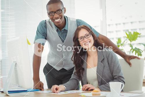 Smiling business professionals working at computer desk