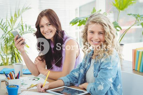 Portrait of smiling business team using technology while sitting at desk