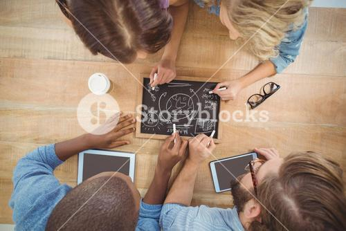 Overhead view of people writing business terms on slate