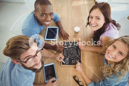 Overhead portrait of smiling business people writing business terms on slate