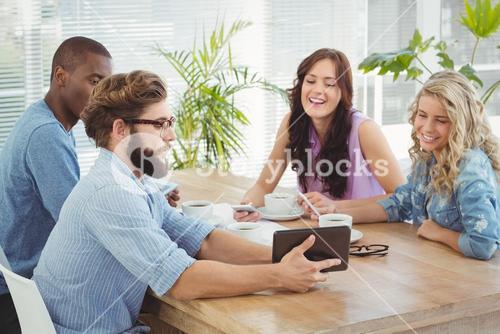 Man showing digital tablet to coworkers at desk