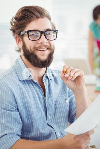 Portrait of smiling man holding pen and paper