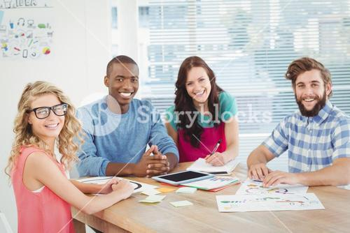 Portrait of smiling business professionals at desk