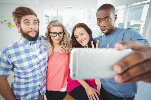 Business people making face while taking selfie