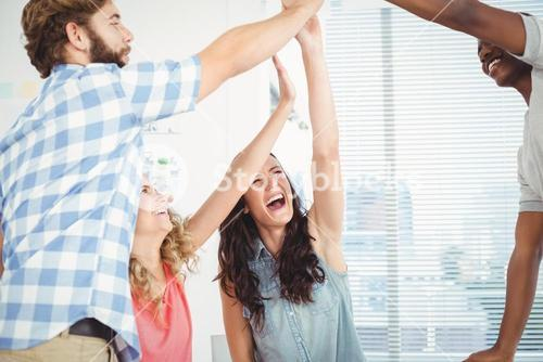 Smiling business professionals giving high five at desk