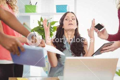 Depressed businesswoman gesturing at desk