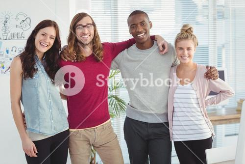 Portrait of smiling business team with arms around