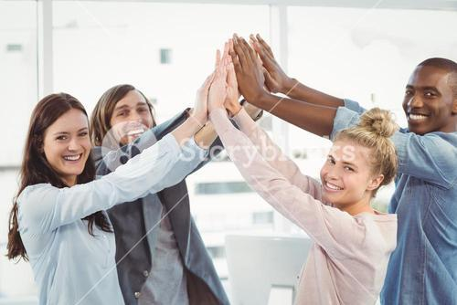 Portrait of smiling business team giving high five