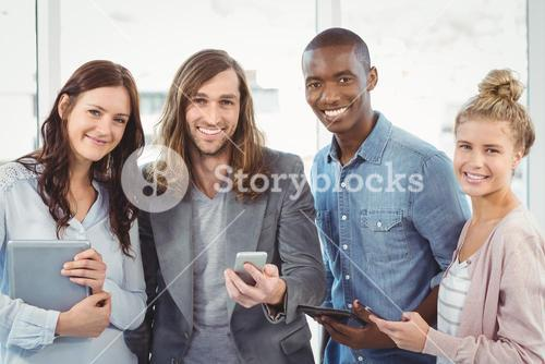 Portrait of smiling business team using technology