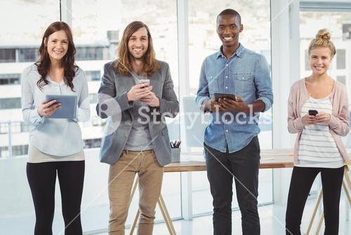 Portrait of cheerful business team using technology