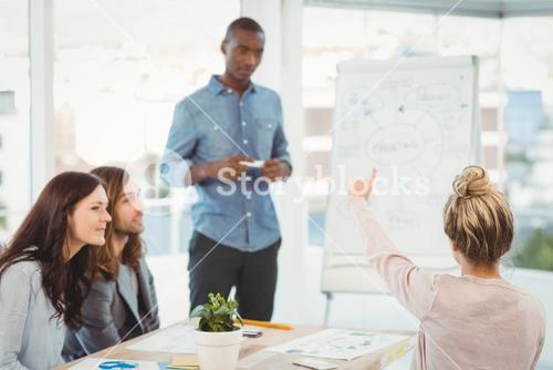Rear view of woman with hand raised while discussing with coworkers