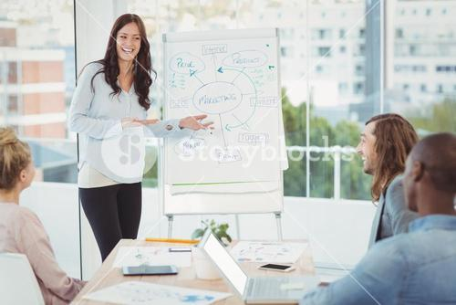 Smiling woman showing flowchart on white board