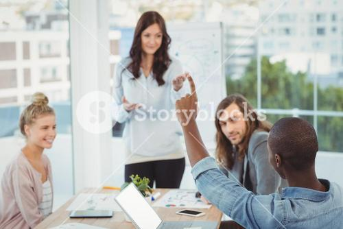 Man with hand raised while discussing with coworkers