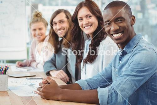 Portrait of smiling business people sitting in row at desk