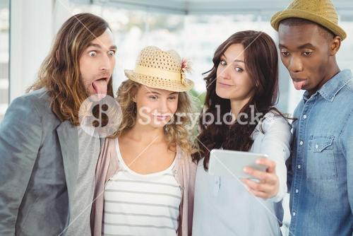 Business team making face while taking selfie