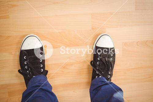 Businessman wearing canvas shoes standing on hardwood floor