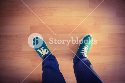Man with canvas shoes on hardwood floor