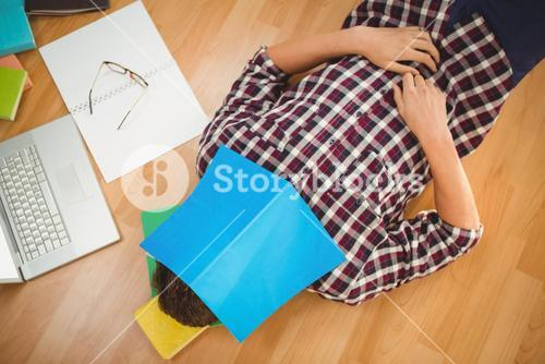 Creative businessman lying on hardwood floor