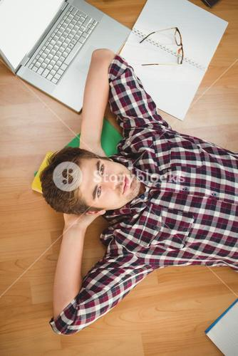 Hipster with hands behind head lying on hardwood floor