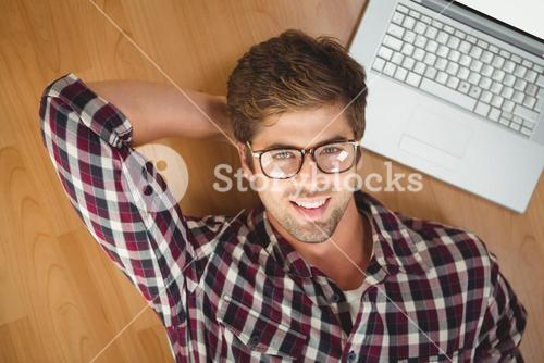 Hipster smiling while lying by laptop on hardwood floor
