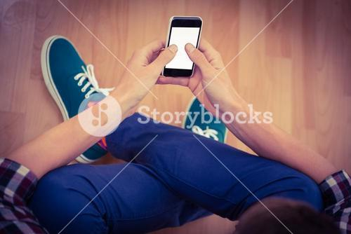 Hipster using smartphone while sitting on hardwood floor
