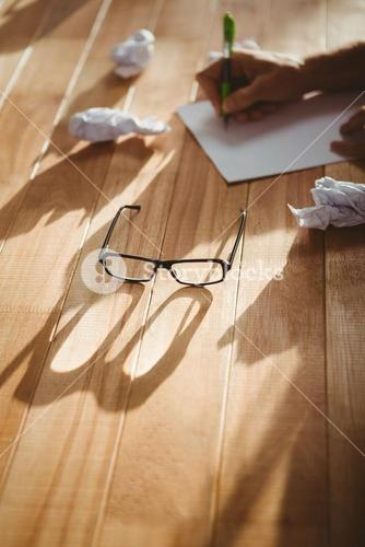 Eye glasses by man writing at desk in office