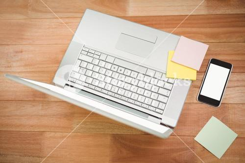 Laptop with sticky notes and smartphone at desk