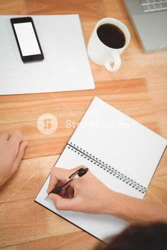 Man writing on spiral notebook at desk in office