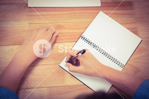 Businessman writing on spiral notebook at desk in office