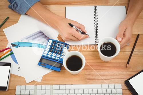 Hipster holding coffee while writing on spiral notebook