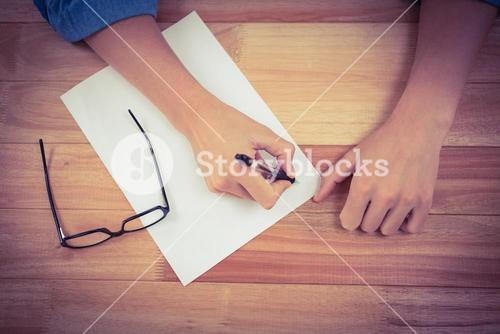Man writing in paper at desk