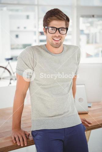 Happy hipster wearing eye glasses leaning at desk