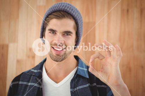 Portrait of happy hipster showing OK sign