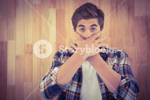 Portrait of shocked man covering mouth