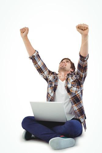 Hipster with laptop on lap cheering with arms raised